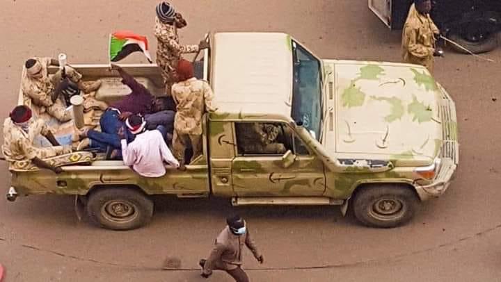 """صورة متظاهر في الخرطوم يرفع علم السودان داخل سيارة الأمن """"تاتشر"""" تشعل مواقع التواصل الإجتماعي"""