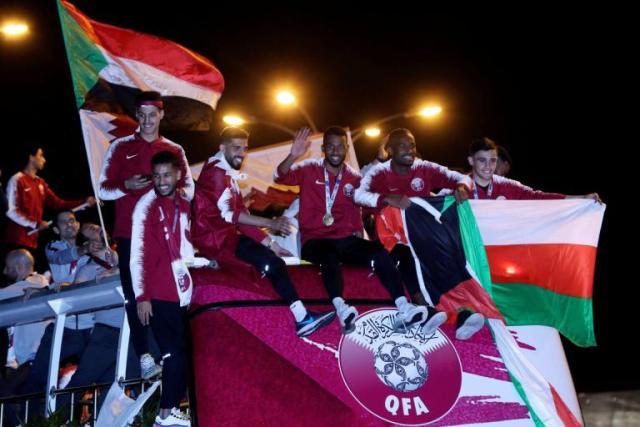 """بالصور.. أحد لاعبي """"قطر"""" يرفع علم """"السودان"""" خلال احتفالات بكأس آسيا ونشطاء سودانيين: (شكراً للناس الما نست أصلها)"""