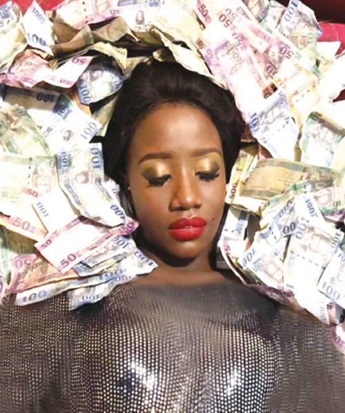 بالصور: فنانة يوغندية تسبح وسط أموال من عـملة الجنوب