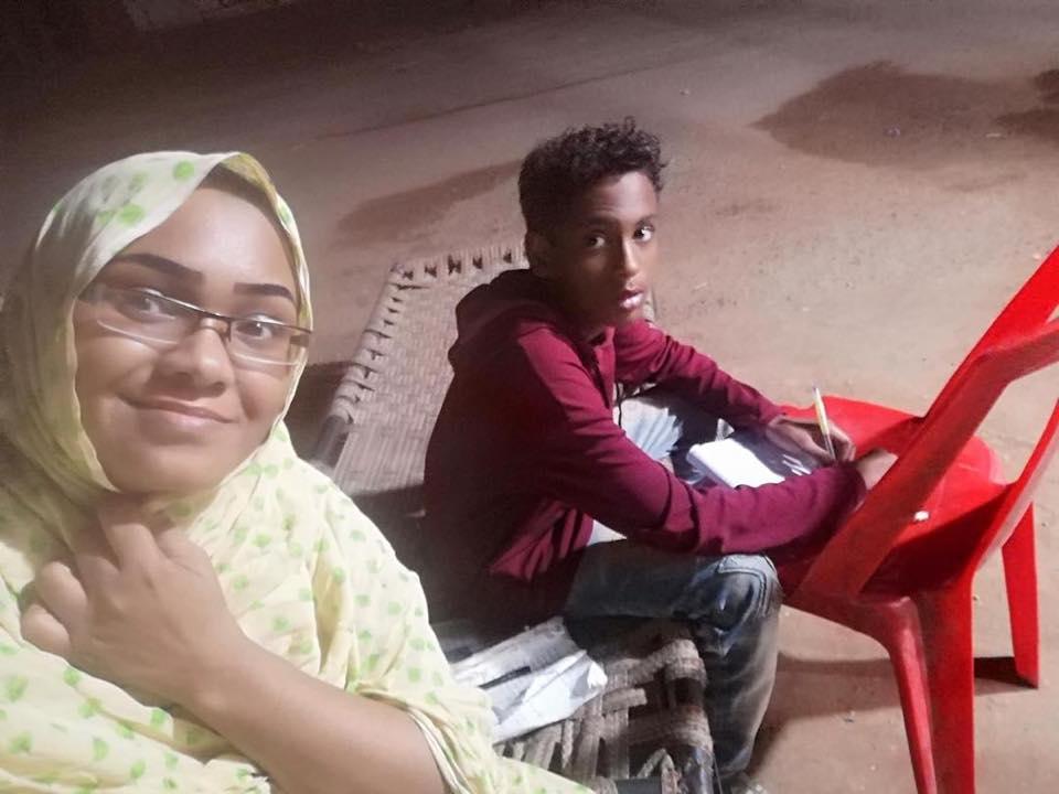 """شاهد بالصور.. قطوعات الكهرباء تدفع أم سودانية لاصطحاب ابنها الطالب للمذاكرة تحت أضواء """"بقالة"""" وتقول: (أشهد يا تاريخ في عام 2020 ولدي يقرأ في الشارع)"""